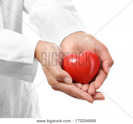 Red plastic heart in female hands on white background, closeup