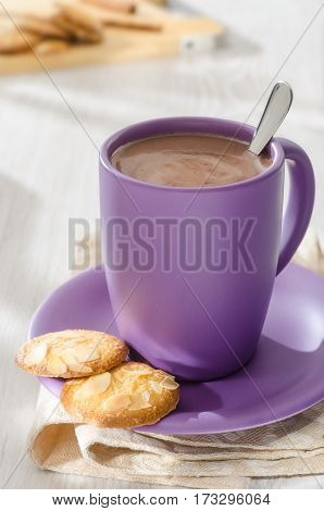 cup of hot chocolate and almond flakes cookies on plate