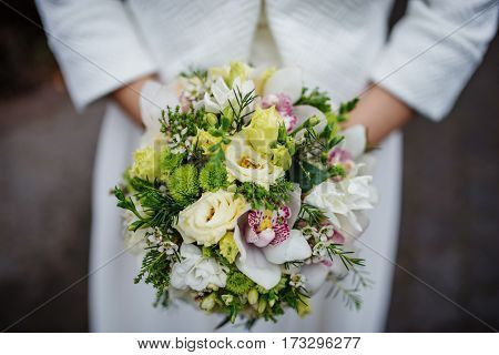 Elegant Green Wedding Bouquet At Hands Of Bride.