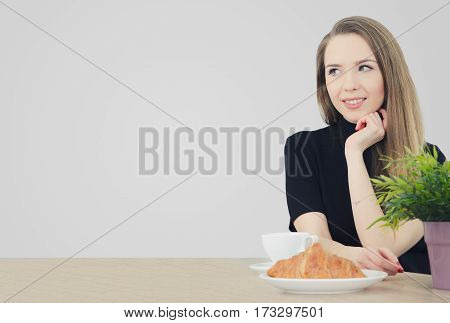 Woman Sitting At A Table With Coffee And Croissant