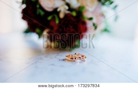 Wedding Rings On Table At Cafe Against Wedding Bouquet.