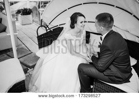 Charming Wedding Couple Sitting In A Bungalow. Black And White Photo.