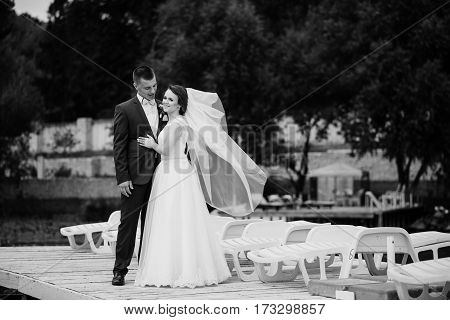 Charming Wedding Couple Hugging On Pier Of The Dock. Black And White Photo.