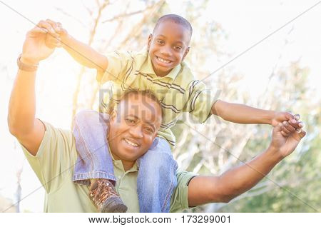 Happy African American Father and Son Riding Piggyback Outdoors At The Park.