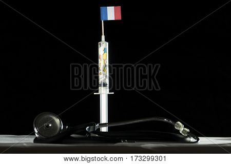 Stethoscope And Syringe Filled With Drugs Injecting The French Flag On A Black Background