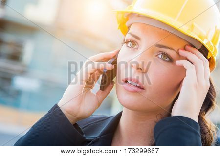 Young Worried Looking Professional Female Contractor Wearing Hard Hat at Construction Site Using Cell Phone.