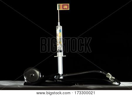 Stethoscope And Syringe Filled With Drugs Injecting The Sri Lankan Flag On A Black Background