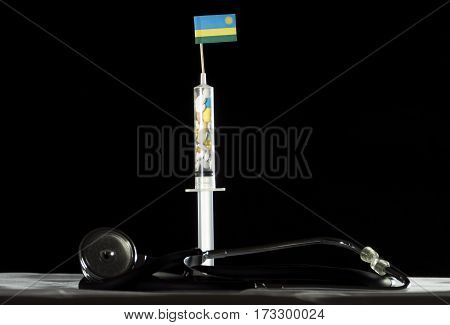 Stethoscope And Syringe Filled With Drugs Injecting The Rwandan Flag On A Black Background