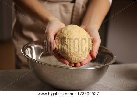 Young woman making dough in kitchen, closeup