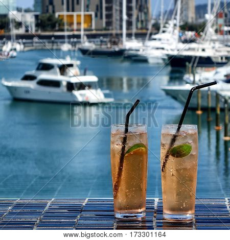 Cold lime drinks in glasses on dark table outside with harbor in background