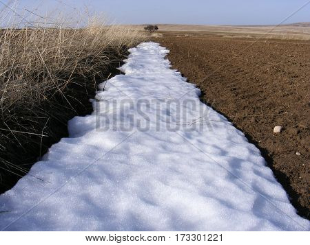 The arrival of spring in the continental climate, snow and cultivated fields