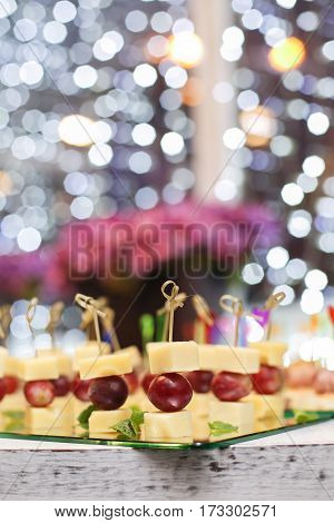 Appetizer of grape, pineapple cubes and cheese are on wooden skewers