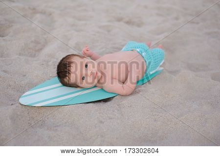 Two week old newborn baby boy lying on a tiny turquoise blue and white surfboard. He is wearing aqua colored board shorts and lying on a sandy beach.