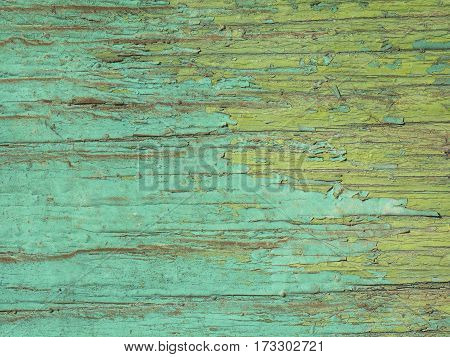 The texture of cracked blue and green paint on wood