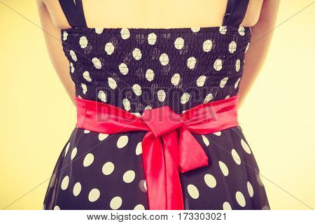 Retro pin up elegant and timeless clothes concept. Woman wearing retro dotted black dress with big red bow