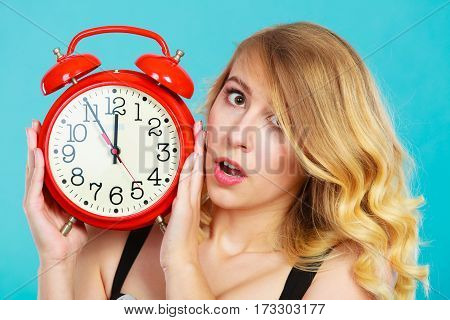 Management time concept. Closeup blonde emotional girl shocked expression with alarm clock on blue.