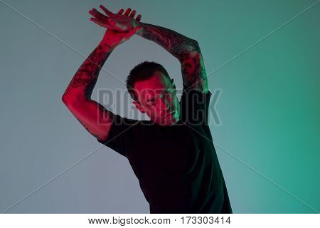 Portrait of sport fit attractive man making arm stretch. Masculine tattooed hands hipster look. Color flash studio light