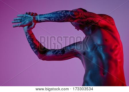 Fashion shoot of sport fit attractive man making arm stretch. Masculine naked body tattooed hands hipster look. Color flash studio light