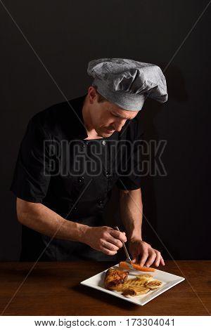 chef preparing a chicken dish with garnish
