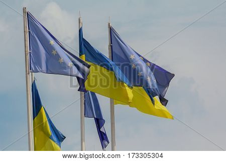 Ukrainian and European Union flags develop on sky background