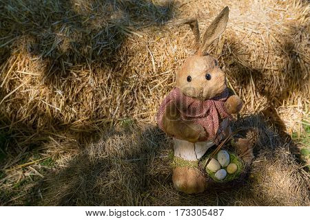 Toy rabbit with Easter eggs in the yard