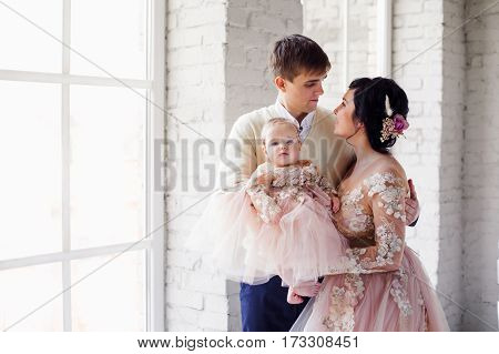Happy family with a young daughter. Mom and baby in beautiful dresses