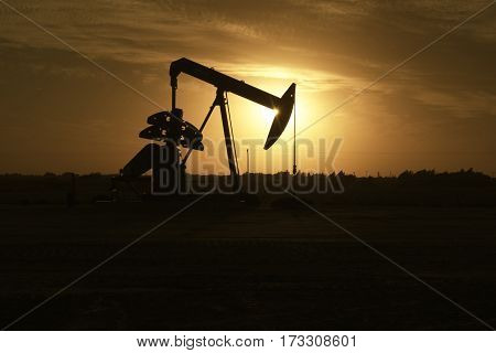 Oil pump jack silhouetted by sunset in oil field