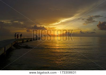 People look in water on dock at sunset