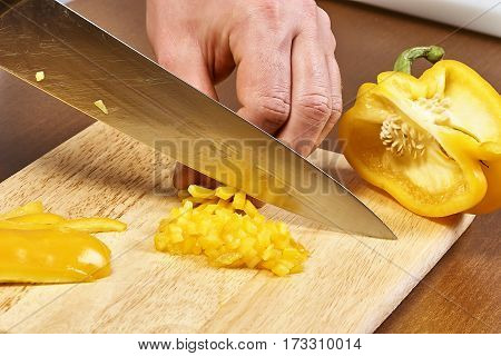 closeup on hands cutting yellow pepper on professional kitchen food recipe