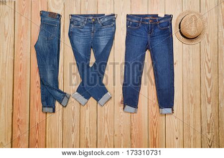 Three blue Jeans with hat and wooden board