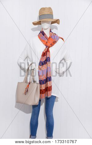 female in jeans with hat and scarf,bag on mannequin-white wooden background