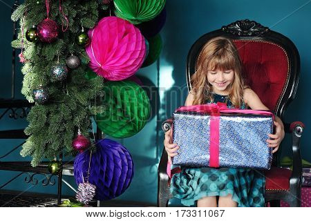 Merry Christmas. Pretty young girl near Christmas tree decorated with colorfull big paper balls, with beautifuly decorated gifts