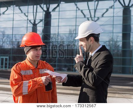 The manager giving the envelope with money to the builder and showing shh gesture.
