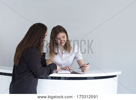young female receptionist at medical clinic or hospital discussing schedule with patient and writing record to the note book .