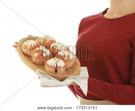 Woman in apron holding plate with muffins on white background