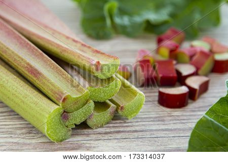 Fresh red and green rhubarb on wooden background