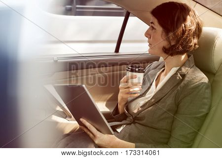 Businesswoman using digital tablet on backseat of the car