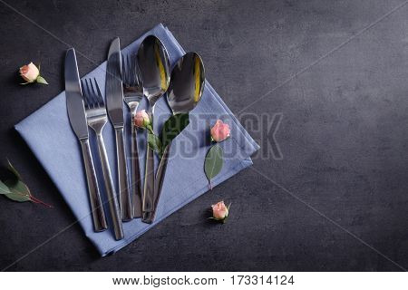 Set of silverware with napkin on grey background