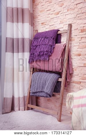 Decorative ladder with plaids near brick wall in living room