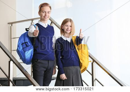 Cute boy and girl in school uniform standing on stairs and showing thumb up gesture