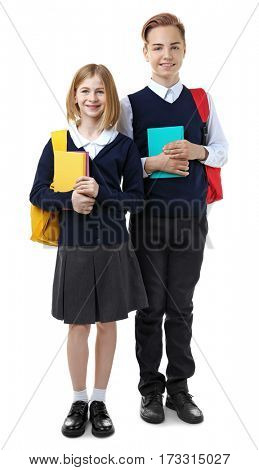 Cute girl and boy in school uniform holding books on white background