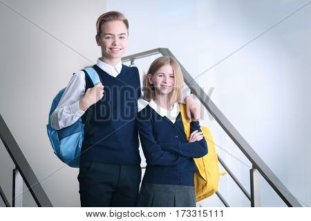 Cute boy and girl in school uniform standing on stairs