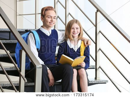 Cute boy and girl in school uniform sitting on stairs and reading book