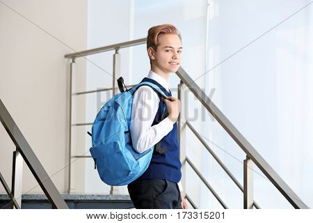 Teenage boy in school uniform with backpack standing on stairs