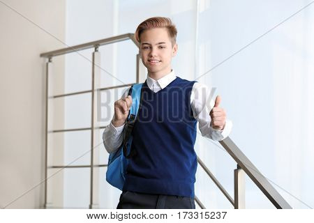 Teenage boy in school uniform showing thumb up gesture standing on stairs