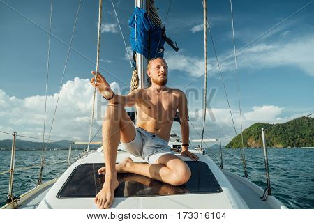 Bearded young man with a mustache sitting on the deck of sailing boat during a walk on the sea. Luxury travel.
