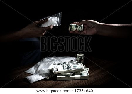 Hand out to send money to buy the drugs many banknote and drugs on wooden table concept about the drug problem drug addiction and has been trading.