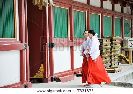 Fukuoka Japan: December 16 2009 -Unidentified miko Japanese maiden walking inside the famous Dazaifu Tenmangu