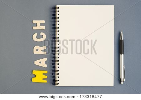 Top view of spiral open notebook with pen and March month wording on grey background
