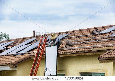 Man Installing solar panels on residential roof